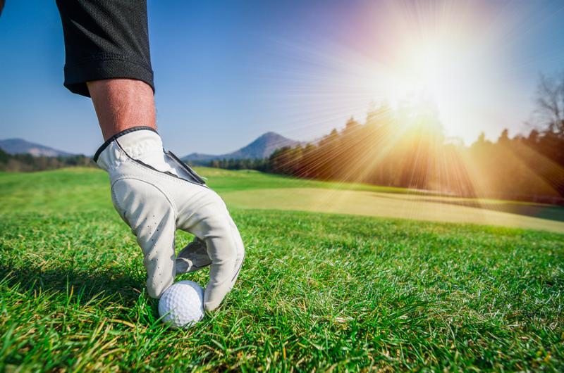 photo of gloved hand placing golf ball on grass