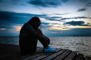 photo of sad woman on boat dock