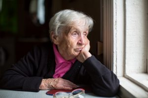 photo of older woman looking out window