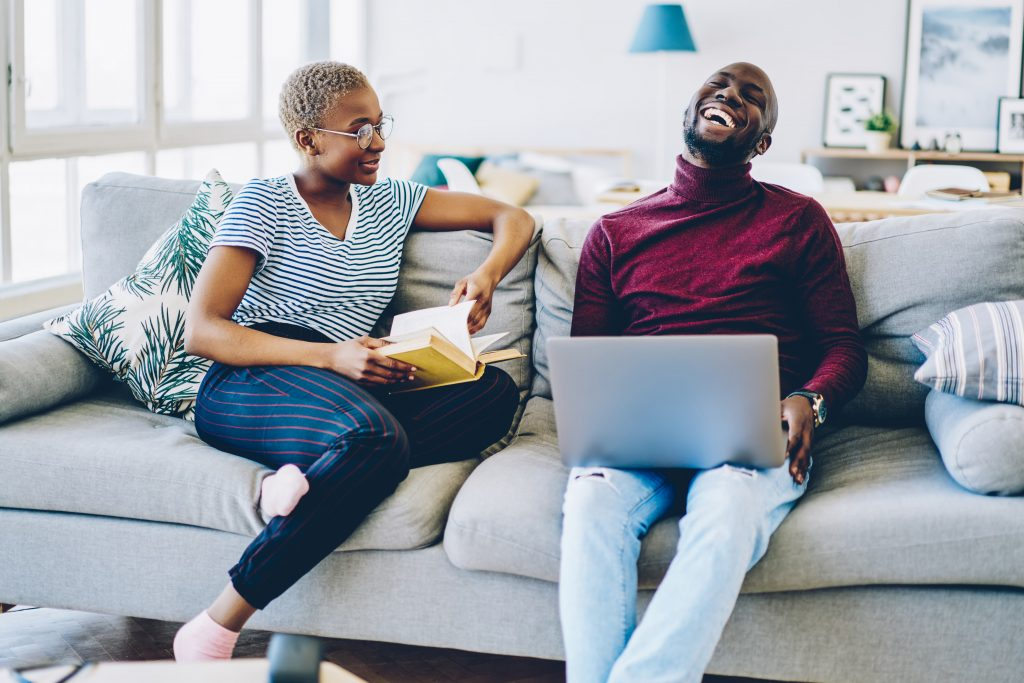 African American couple working from their couch at home