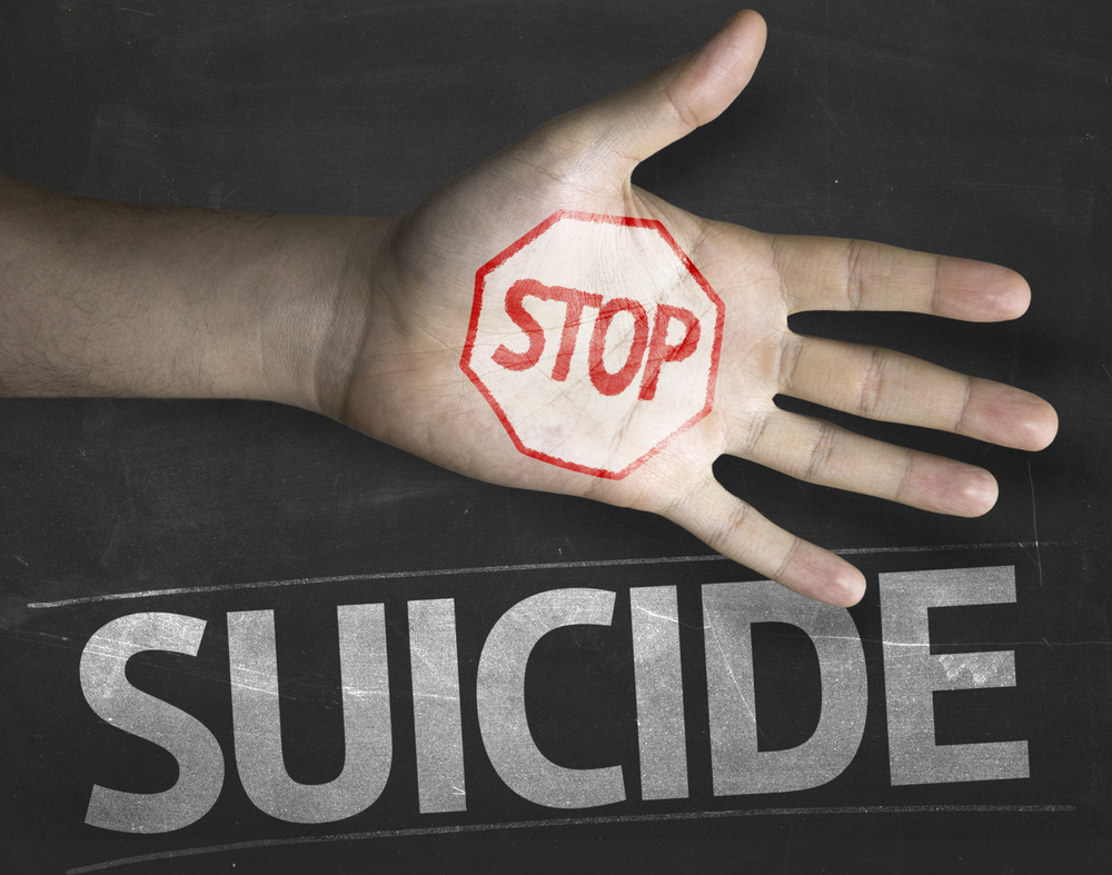 hand outstretched with words stop suicide