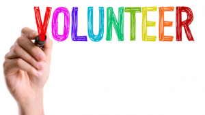 hand writing the word 'volunteer'